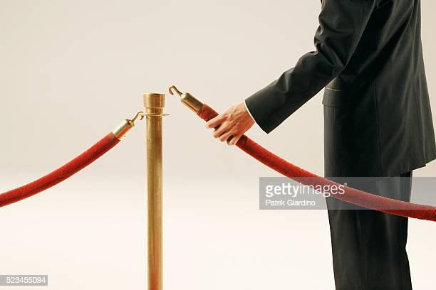 Man Holding Velvet Rope