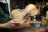 Man holding  violin in workshop for restoration