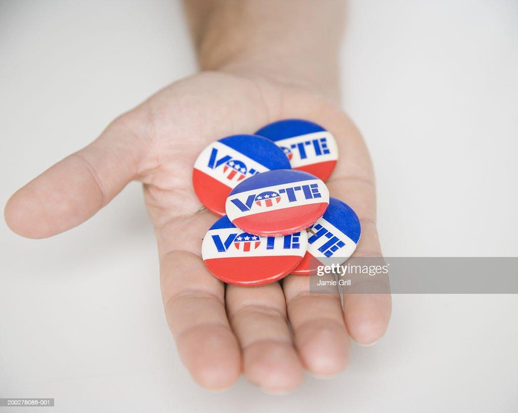Man holding 'VOTE' buttons, close-up : Foto de stock