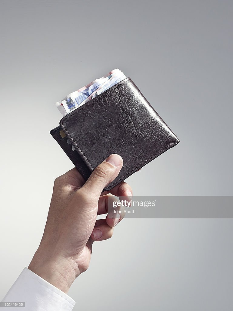 Man holding wallet, close-up of hand