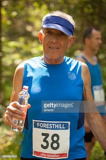 Mann hält eine Flasche Wasser während ultramarathon Das training für ein Rennen