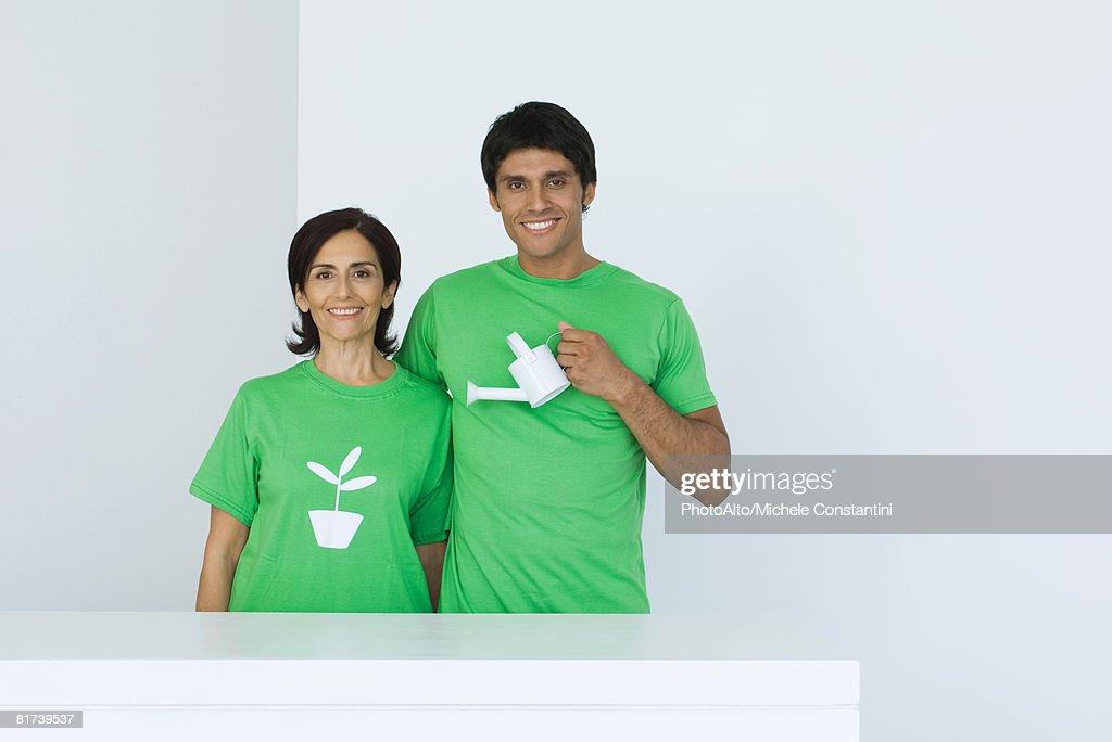 Man holding watering can, standing beside woman wearing tee-shirt printed with plant graphic, portrait