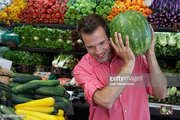 Man holding watermelon to ear in supermarket, close-up