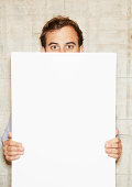 man holding white message board