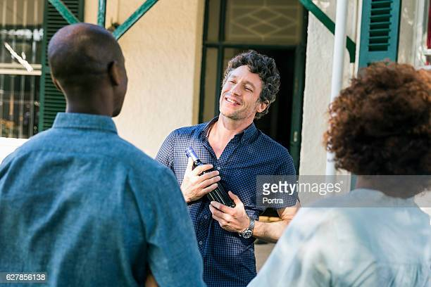 Man holding wine bottle while looking at friends