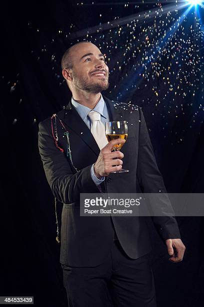 Man holding wine, smiling up at a new year party
