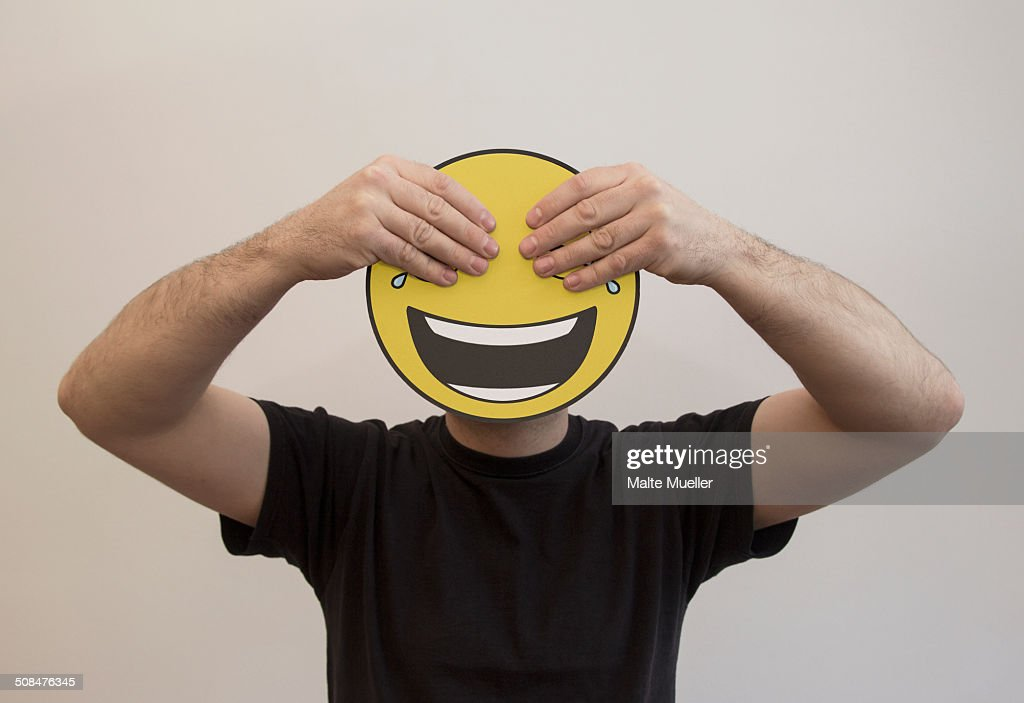 Man holding with hands covering the eyes of a happy emoticon face