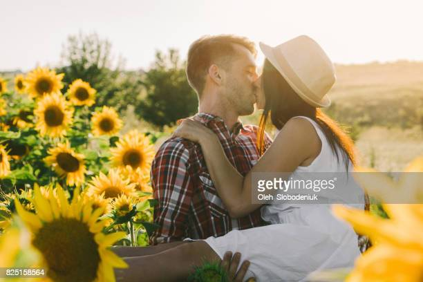 Man holding woman on hands in  sunflower field at sunset