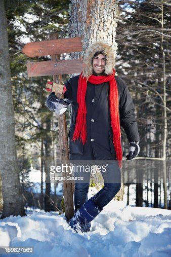 Man holding wooden sign in forest