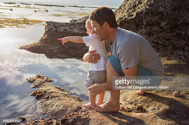 Man holding young boy, looking out to sea