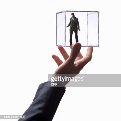 Man holding young businessman in transparent box (Digital Composite) : Stock Photo
