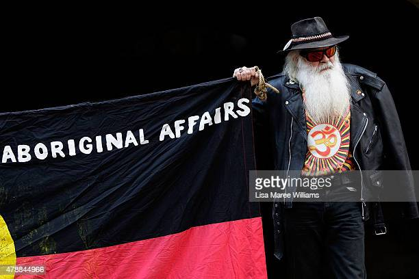 A man holds a Aboriginal flag during a protest at Sydney Town Hall against the Governments treatment of Aboriginals on June 28 2015 in Sydney...