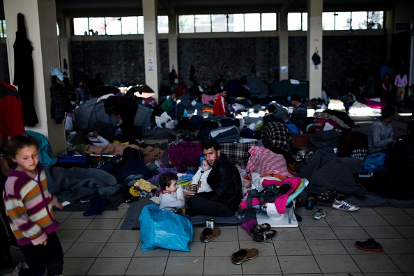 A man holds a baby inside a passenger terminal used as a shelter for refugees and migrants at the Piraeus harbour in Athens on March 21, 2016. A total of 1,662 migrants have landed on Greek islands...