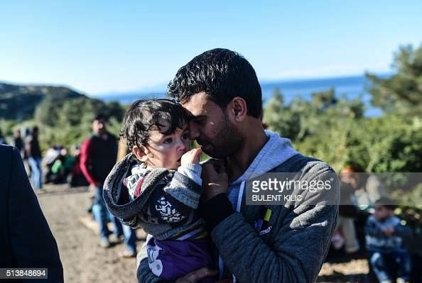 A man holds a baby on the side of a road after being detained by Turkish soldiers with other Syrians trying to reach the Greek island of Lesbos from...