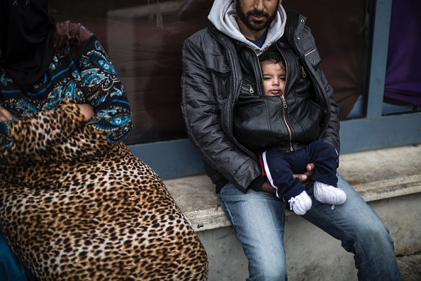 TOPSHOT - A man holds a baby outside a passenger terminal used as shelter for refugees and migrants in the Piraeus harbour in Athens on March 12, 2016. Greece aims to deal swiftly with the migrant ...