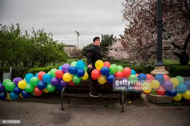 TOPSHOT A man holds a balloon garland prior to an antiabortion rally in Bucharest on March 25 2017 The movement is supported by the Romanian Ortodox...