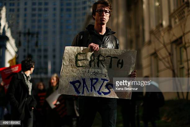 A man holds a banner as he takes part in a global climate march near City Hall on November 29 2015 in New York City The protest is part of an...