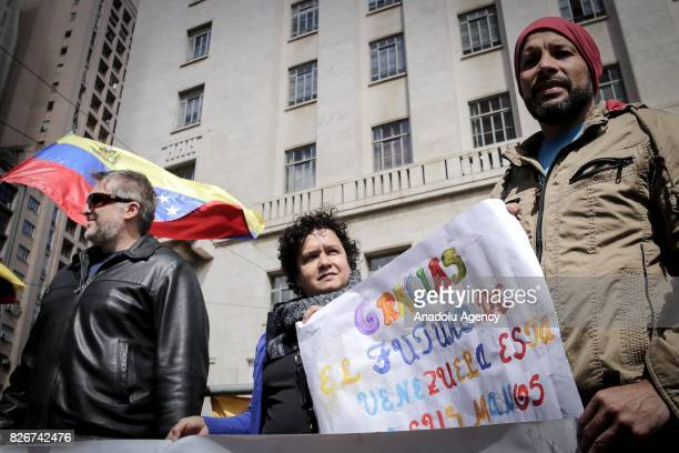 A man holds a banner as people gather to stage a demonstration while Foreign Ministers of Brazil Argentina Paraguay and Uruguay hold a meeting on...