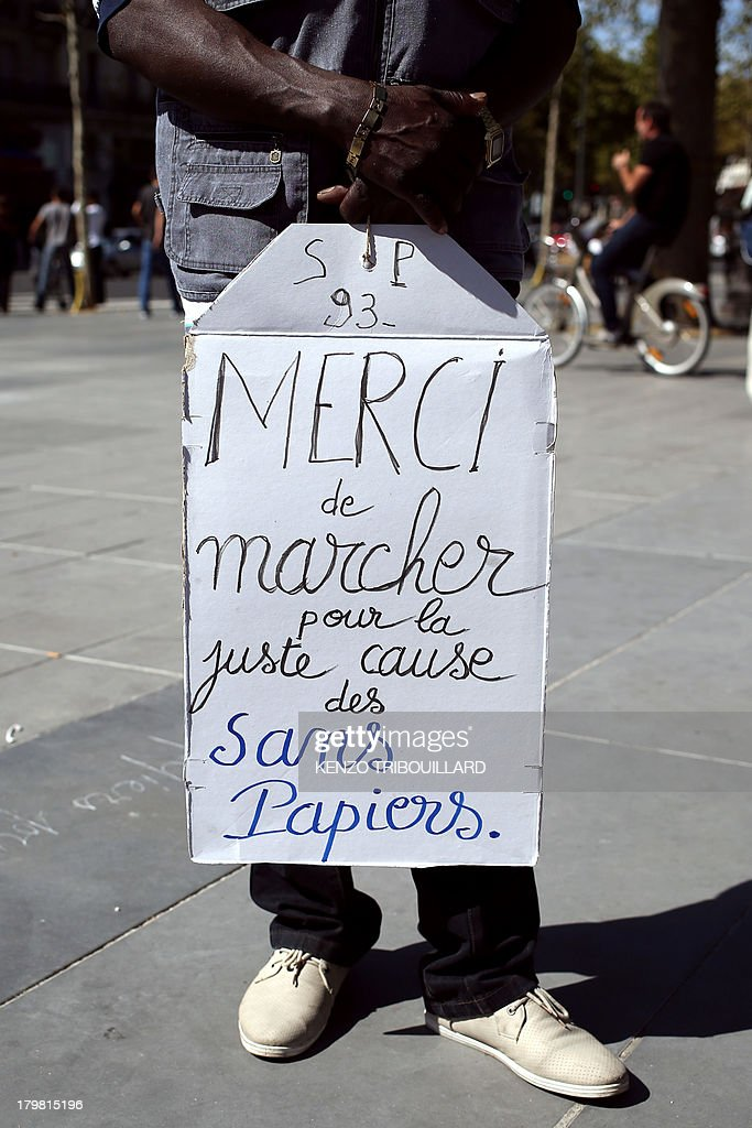 A man holds a banner calling for the support of undocumented immigrants during a demonstration demanding their legalisation in Paris on September 7, 2013.