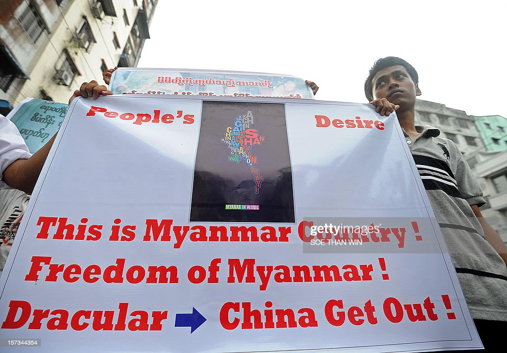 A man holds a banner during a protest in Yangon on December 2, 2012 against a Chinese-backed copper mine in Monywa in northern Myanmar. At least two people have been arrested at a rally in Yangon held to condemn a violent police crackdown on protesters at a Chinese-backed copper mine, an activist and an AFP reporter said. AFP PHOTO / Soe Than WIN