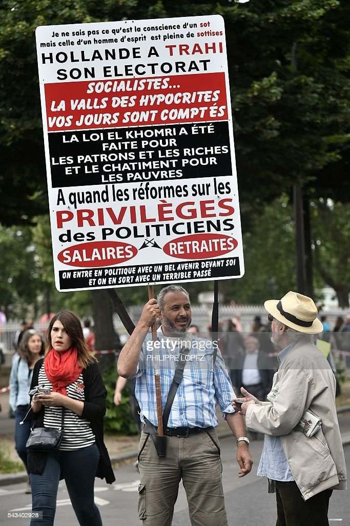 A man holds a banner reading 'Hollande betrayed his electorate. Socialists, The Valls of hypocriticals, your days are counted. The El Khomri's law was made for bosses and rich people and for the punishment of poor people. When can we expect reforms on politician's privileges, salaries and retirement' during a demonstration against controversial labour reforms, on June 28, 2016 on Bastille Square in Paris. Unions have called repeated strikes and marches in opposition to the law, which seeks to bring down France's intractable 10-percent unemployment rate by making it easier to hire and fire workers. / AFP / PHILIPPE