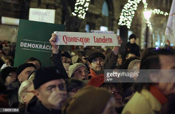 A man holds a banner reading in latin ''How long yet'' an extract of a quote by Roman philosopher Cicero during a demonstration gathering tens of...