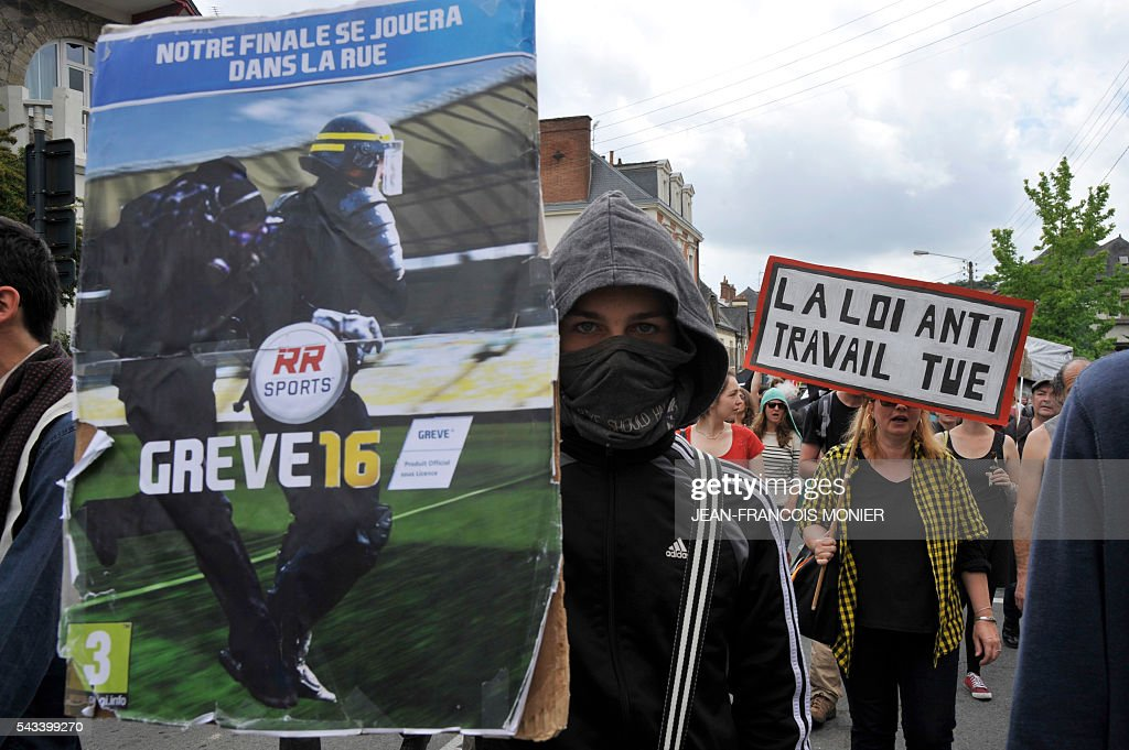 A man holds a banner reading 'Our finale will be played in the street, Strike16' during a demonstration against controversial labour reforms, on June 28, 2016 in Rennes. Unions have called repeated strikes and marches in opposition to the law, which seeks to bring down France's intractable 10-percent unemployment rate by making it easier to hire and fire workers.