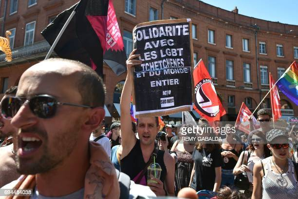 A man holds a banner reading 'Solidarity with LGBT from Chechnya and from all over the world' as they take part in the Lesbian Gay Bisexual...