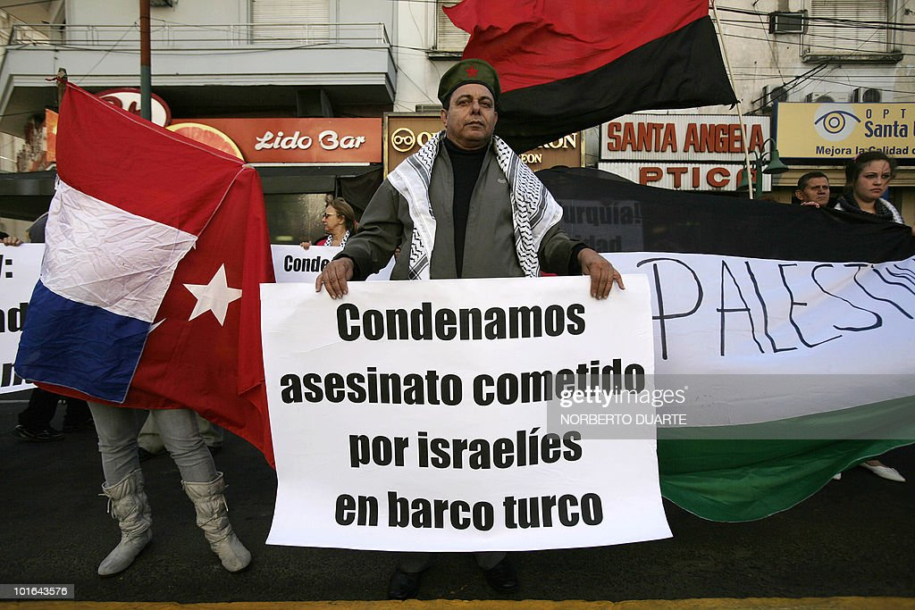 A man holds a banner reading 'We condemn the murder committed by Israelis on Turkish ship' during a demonstration in support of Palestine in Asuncion on June 5, 2010. Earlier this week the Freedom Flotilla, a fleet of ships with international humanitarian aid for the Palestinians in the Gaza Strip, was raided by the Israeli army. Nine activists were killed and several more were injured. AFP PHOTO/Norberto duarte