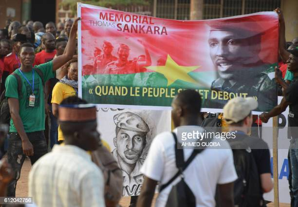A man holds a banner reading 'When the people stands up' as he attends a demonstration in tribute to former president Thomas Sankara in Ouagadougou...