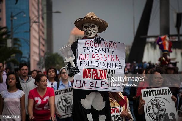 A man holds a banner that reads in spanish 'Deceitful Government that kills students we lack 43 it was the state' during a protest against Mexican...