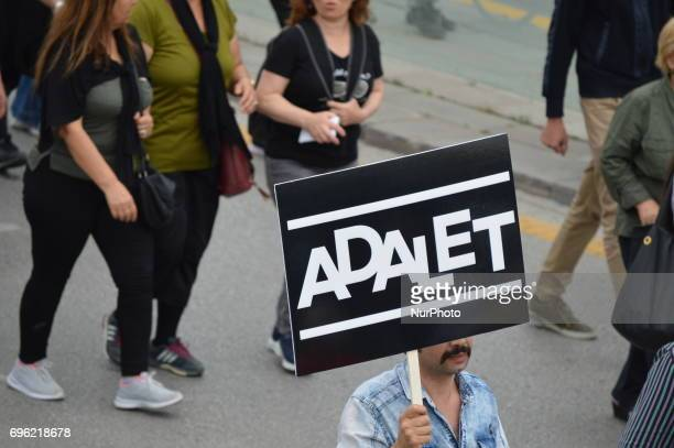A man holds a banner that reads 'Justice' in Turkish during the 'Justice March' to protest against the Turkish government held by the main opposition...