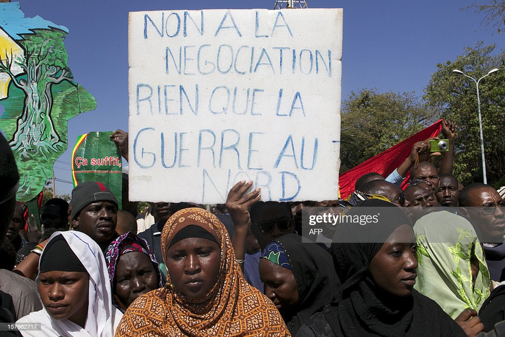 A man holds a banner that reads 'No to negotiation, only war in the north' as thousands of Malians gather in Bamako on December 8, 2012 to take part in a demonstration called by several Malian political parties to support the Malian army and demand a United Nations (UN) Security Council resolution approving the deployment of an international force in the country's north, controlled for eight months by Islamist armed groups. Facing the international community's equivocation on the matter, impatience rises in Mali's people, who say they are ready to go to war to take their 'own destiny in hand'.