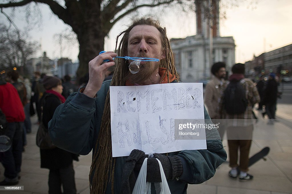 A man holds a banner while blowing bubbles as people gather to mark the death of former premier Margaret Thatcher in the Brixton district of London, U.K., on Monday, April 8, 2013. Thatcher, the former U.K. prime minister who helped end the Cold War and was known as the 'Iron Lady' for her uncompromising style, died today. She was 87. Photographer: Simon Dawson/Bloomberg via Getty Images