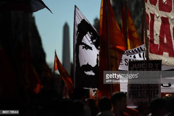 A man holds a banner with an image of Santiago Maldonado a missing activist who disappeared two months ago during a police operation in Chubut and...