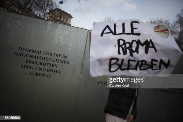 A man holds a banner with the written slogan 'Alle Roma Bleiben' as ethnic Roma protest in front of the Memorial for under Nazism murdered Sinti and...