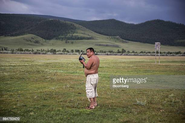 A man holds a batterypowered mobile phone in Ikh Tamir Mongolia on Wednesday Aug 3 2016 Mongolia a mineralrich and landlocked $12 billion economy...