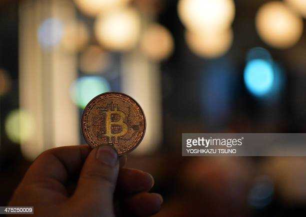 A man holds a bitcoin medal as members of bitcoin trading club hold a meeting in Tokyo on February 27 2014 Bitcoin users in Tokyo gathered for a...