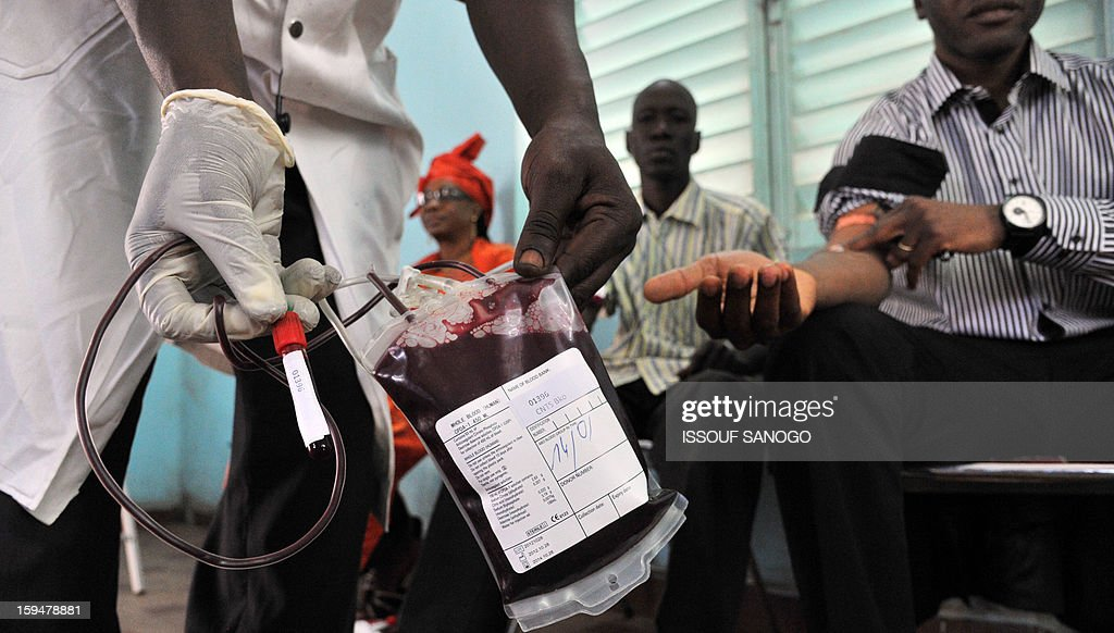A man holds a blodd bag as people donate blood for the injured, on January 14, 2013 in Bamako. Islamists have retreated in the east of Mali but French forces are facing a difficult situation in the west of the country where rebels are well armed, French Defence Minister Jean-Yves Le Drian said on January 14. France launched the operation alongside the Malian army on January 11, 2013 to counter a push south by the insurgents who had threatened to advance on the capital Bamako. AFP PHOTO / ISSOUF SANOG0
