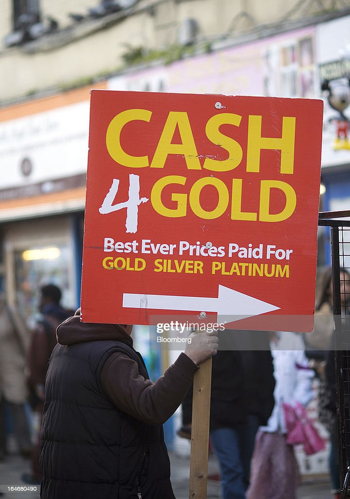 A man holds a board advertising prices for 'Cash 4 Gold' as he stands in the street in Dublin, Ireland, on Saturday, March 16, 2013. Ireland's renewed competiveness makes it a beacon for the U.S. companies such as EBay, Google Inc. and Facebook Inc., which have expanded their operations in the country over the past two years. Photographer: Simon Dawson/Bloomberg via Getty Images