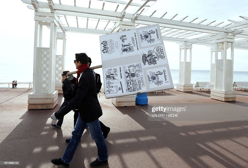 A man holds a board as he demonstrates on the famous 'Promenade des Anglais', on February 12, 2013 in Nice, French Riviera, as part of a nationwide strike day over the government's plans to make children attend classes five days a week, instead of the current four. The government recently issued a decree introducing a half day of school on Wednesdays for children 3 to 11 starting in September, while reducing the school day by 45 minutes the rest of the week.