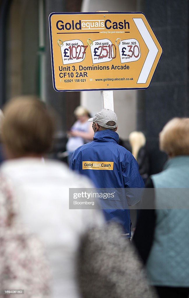 A man holds a board directing customers to a 'cash for gold' store as he stands in the street in Cardiff, U.K. on Thursday, May 23, 2013. Bank of England Markets Director Paul Fisher said policy makers must continue to provide support to the British economy so that companies and consumers have room to reduce debts and rebuild confidence. Photographer: Simon Dawson/Bloomberg via Getty Images
