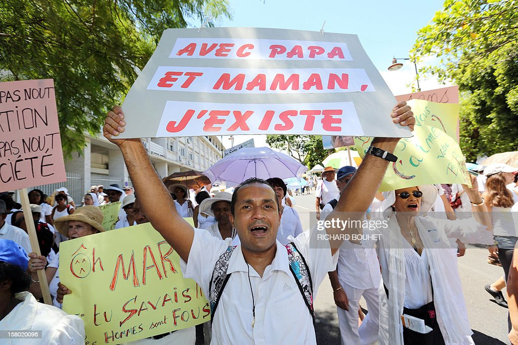 'Dad, Mum, I exist' during a demonstration called by a group of associations which support the same-sex marriage, on December 9, 2012, in Saint-Denis de la Reunion, on the French Indian Ocean island of La Reunion. France's Socialist government adopted on November 7, 2012 a draft law to authorise gay marriage and adoption despite fierce opposition from the Roman Catholic Church and the right-wing opposition.