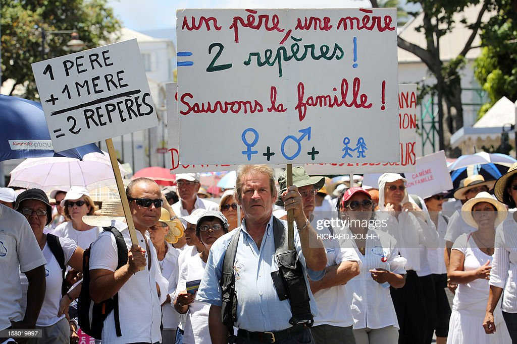 'One father, one mother = two marks, save the family' (center) during a demonstration called by a group of associations which support the same-sex marriage, on December 9, 2012, in Saint-Denis de la Reunion, on the French Indian Ocean island of La Reunion. France's Socialist government adopted on November 7, 2012 a draft law to authorise gay marriage and adoption despite fierce opposition from the Roman Catholic Church and the right-wing opposition.