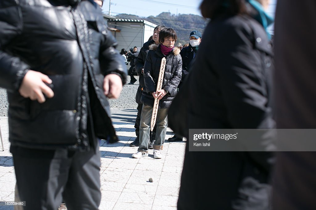 A man holds a board with the name of a victim during a memorial service at a temporary Kouganji Temple on March 11, 2013 in Otsuchi, Iwate, Japan. The original temple was washed away during the tsunami two years ago. On March 11 Japan commemorates the second anniversary of the magnitude 9.0 earthquake and tsunami that claimed more than 18,000 lives.