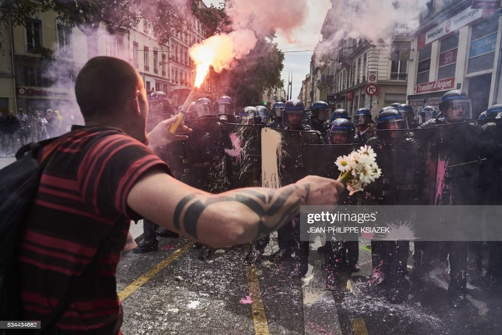 A man holds a bouquet of flowers and a torch as he faces riot police during a demonstration against the government's planned labour reform, on May 26, 2016 in Lyon, central eastern France. The French government's labour market proposals, which are designed to make it easier for companies to hire and fire, have sparked a series of nationwide protests and strikes over the past three months. Masked youths clashed with police in Paris and striking workers blockaded refineries and nuclear power stations on May 26, 2016 as an escalating wave of industrial action against labour reforms rocked France. KSIAZEK