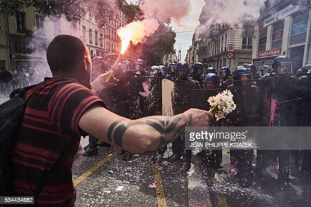 TOPSHOT A man holds a bouquet of flowers and a torch as he faces riot police during a demonstration against the government's planned labour reform on...