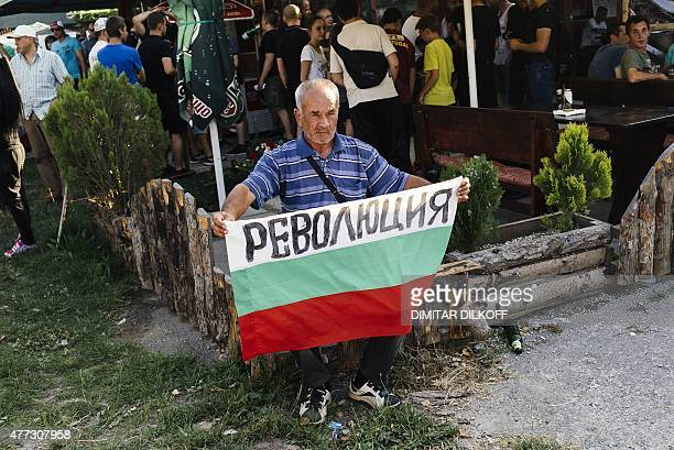A man holds a Bulgarian national flag with the inscription 'revolution' during a protest in Sofia on June 15 2015 as hundreds of people in Sofia's...
