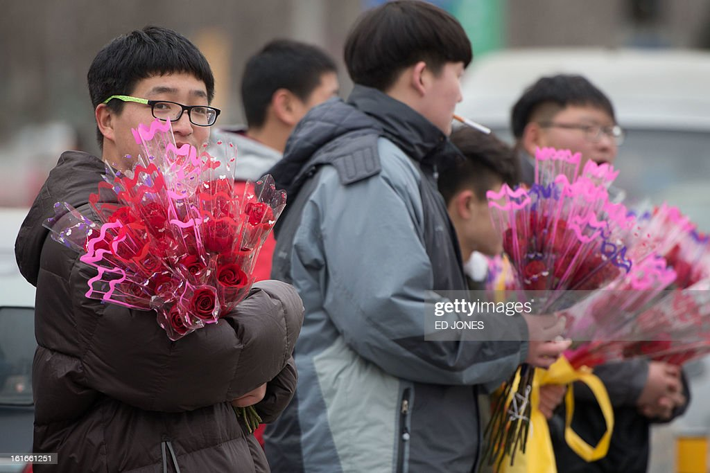 A man holds a bunch of flowers outside a park in Beijing on Febraury 14, 2013. Businesses in the Chinese capital were said to be fearing the proximity of Chinese Lunar New Year falling just days before Valentine's day, after some nine million Beijingers were reported to have left the city for the annual holiday exodous, according to state media. AFP PHOTO / Ed Jones