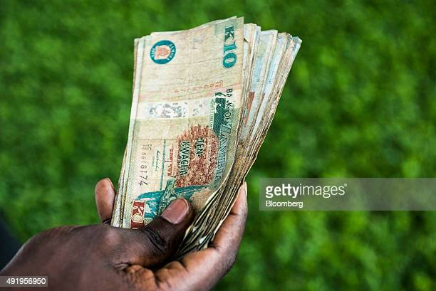 A man holds a bundle of Zambian kwacha banknotes in this arranged photograph in Lusaka Zambia on Thursday Oct 8 2015 Zambian Finance Minister...